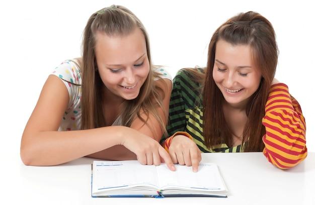 Dwa nastoletniej dziewczyny uśmiecha się książkę odizolowywającą na bielu i czyta