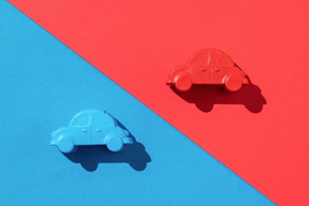 Dwa niebieskie i dwa czerwone samochody na niebieskim i czerwonym tle. pojęcie sprzedaży i kupna samochodów.