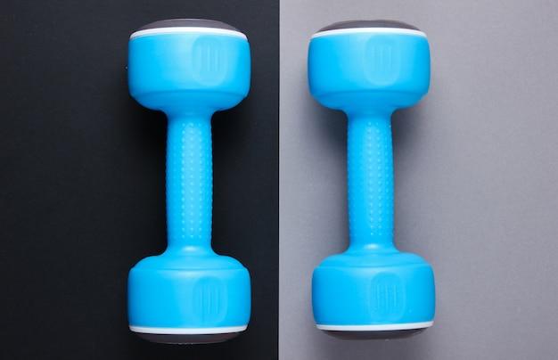 Dwa niebieskie plastikowe hantle na szaro-czarnym stole. widok z góry