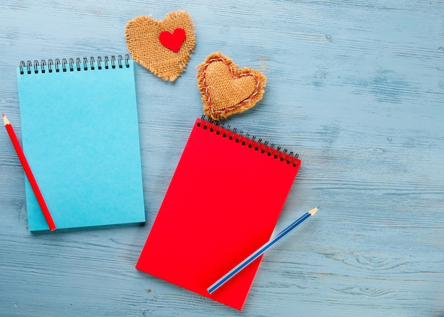 Dwa notatniki i ołówki na niebieskim stole