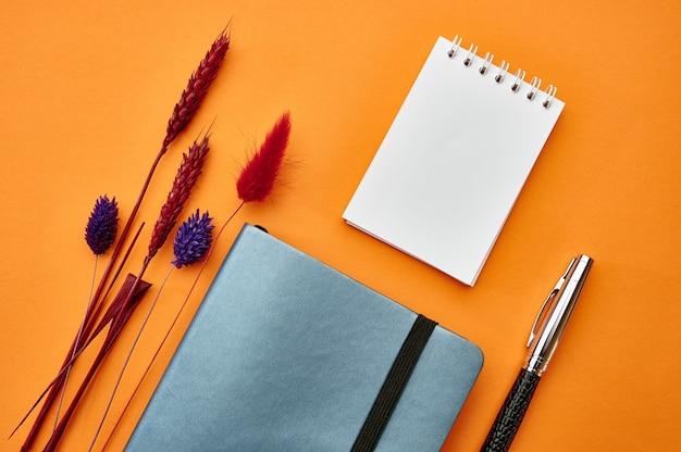 Dwa notesy i zbliżenie pióra, pomarańczowe tło. artykuły biurowe, akcesoria szkolne lub edukacyjne, narzędzia do pisania i rysowania