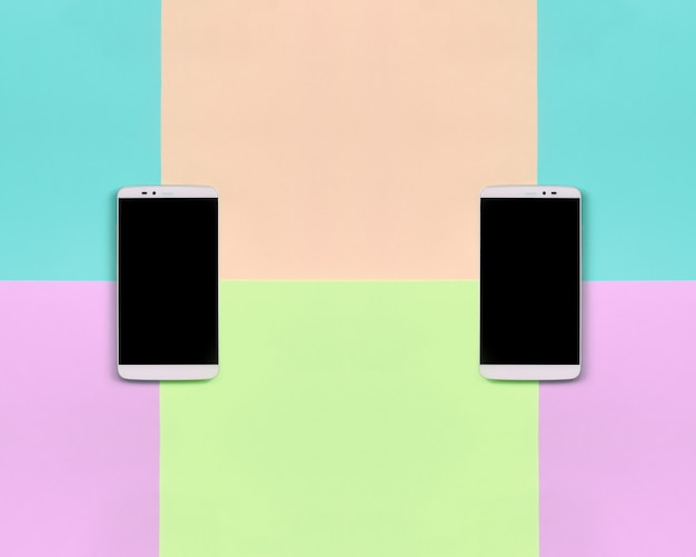 Dwa nowoczesne smartfony z czarnymi ekranami w modnych pastelowych kolorach różowym, niebieskim, koralowym i limonkowym