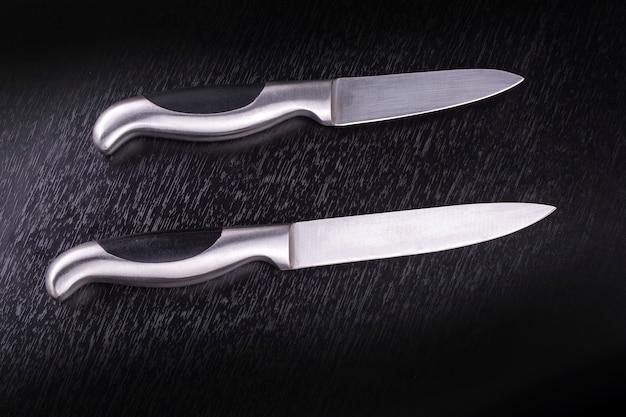 Dwa noże kuchenne na czarnym drewnianym stole