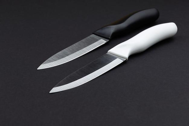 Dwa noże stołowe czarno-białe na czarnym tle
