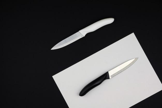 Dwa noże stołowe na czarno-białym biurku