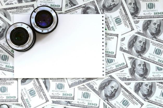 Dwa obiektywy fotograficzne i biały notatnik leżą na tle wielu banknotów dolarowych. miejsce na tekst