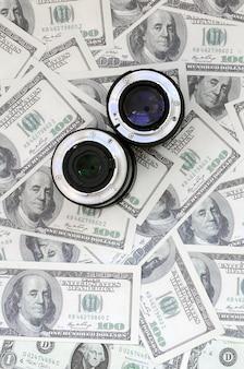 Dwa obiektywy fotograficzne leżą na tle wielu banknotów dolarowych.
