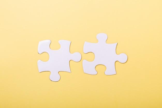 Dwa odłączone kawałki układanki na żółtym tle
