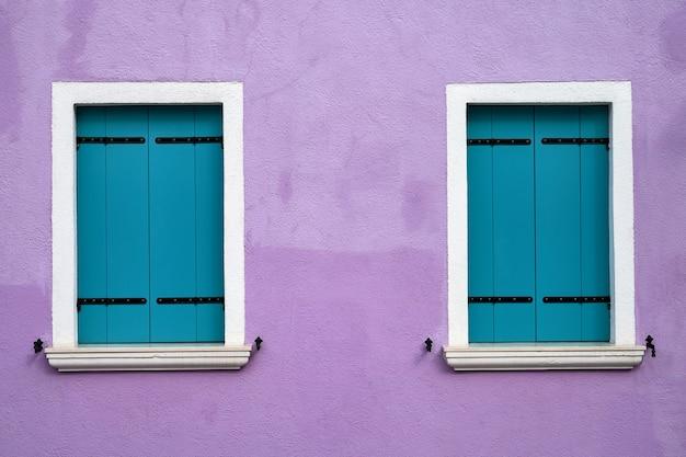 Dwa okna z jasnoniebieskimi okiennicami na starej liliowej ścianie. włochy, wenecja, wyspa burano.