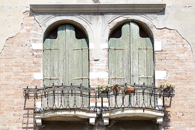 Dwa okna z zielonymi drewnianymi okiennicami i ładnym balkonem na ceglanej ścianie, wenecja, włochy