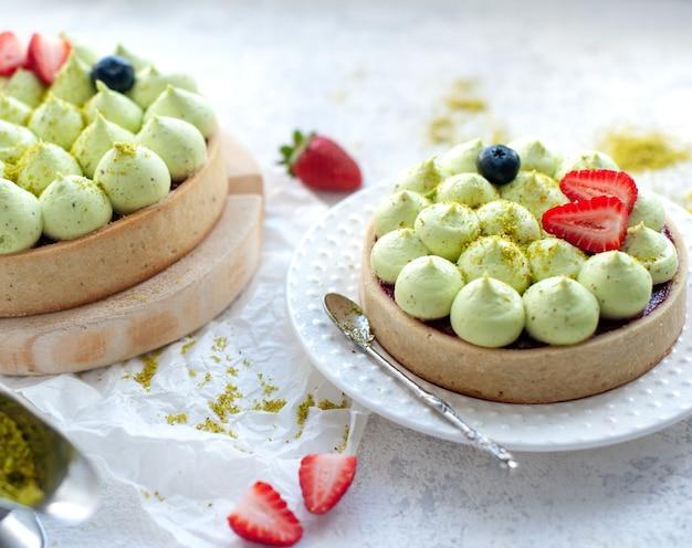 Dwa okrągłe kruche ciasta z zielonym kremem pistacjowym i dżemem truskawkowym, zbliżenie