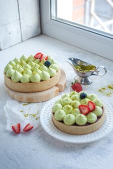 Dwa okrągłe kruche ciastka z zieloną śmietaną pistacjową i dżemem truskawkowym przy oknie