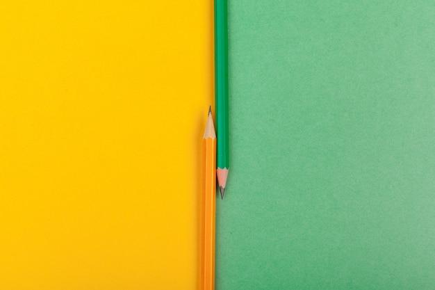 Dwa ołówki leżą na styku dwóch kolorowych papierów: zielonego i żółtego widok z góry
