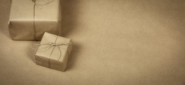 Dwa opakowania prezentowe owinięte zwykłym brązowym papierem i liną oraz teksturą tła brązowego papieru, pudełko retro. obecna koncepcja kopia przestrzeń
