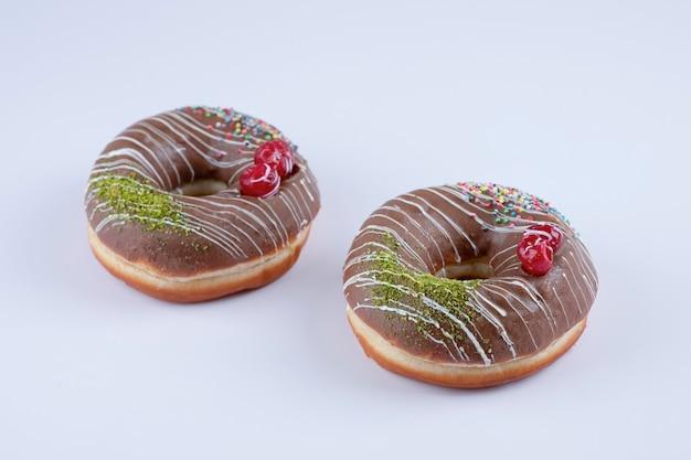 Dwa pączki czekoladowe ozdobione posypką i jagodami na białym tle.
