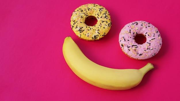 Dwa pączki i banan leżą na różowej powierzchni, tworząc abstrakcję emotikonu - uśmiechu. wzięte z najwyższego punktu