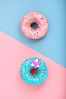Dwa pączki na pastelowym różu i niebieskiej przestrzeni. minimalizm kreatywny skład żywności. płaski układ