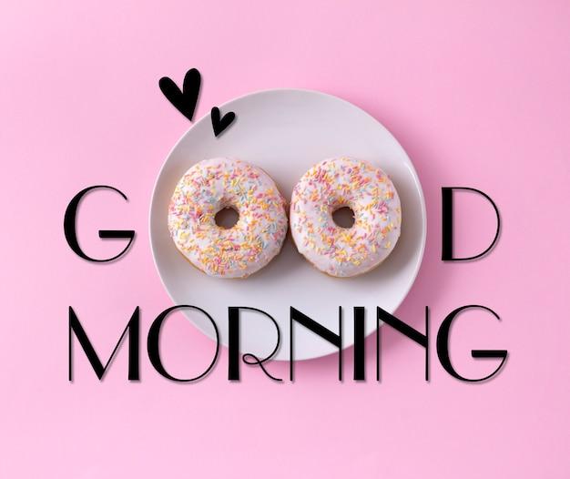 Dwa pączki na talerzu. dzień dobry powitanie napisane na różowo
