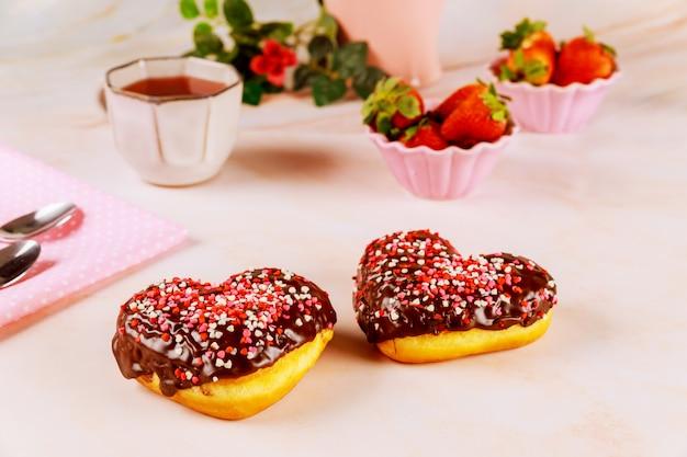 Dwa pączki w kształcie serca z polewą czekoladową i różową, czerwoną posypką na talerzu z truskawkami.