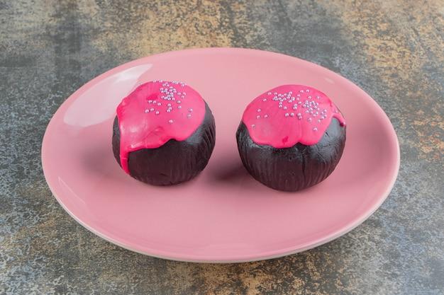 Dwa pączki ze słodkiej czekolady z różowym lukrem i posypką