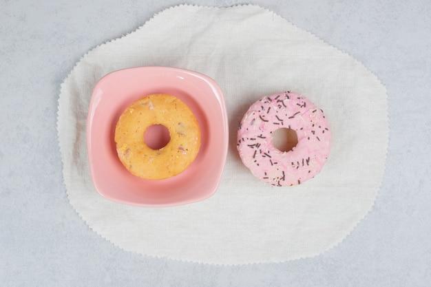 Dwa pączki ze spryskiwaczami na marmurowym stole. wysokiej jakości zdjęcie