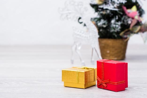 Dwa pakowane prezenty w pudełka i ozdoby świąteczne na szarym tle drewniane. skopiuj miejsce