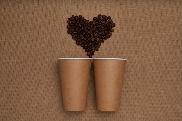 Dwa papierowe kubki z ziarnami kawy w kształcie serca