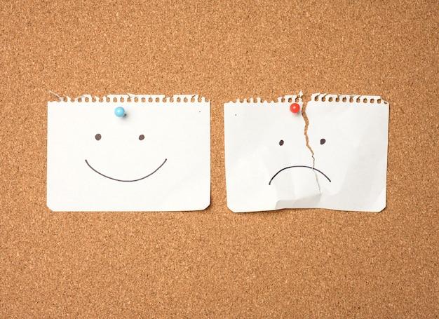 Dwa papierowe listki z uśmiechem i smutną emocją przyczepione guzikiem na brązowej desce, radość i przygnębienie