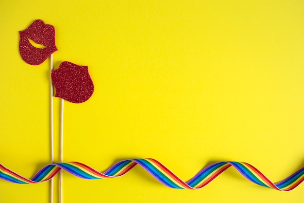 Dwa papierowe pocałunki na patykach w pobliżu wstążki tęczy na żółtym tle.