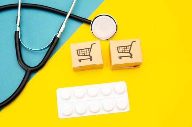 Dwa papierowe pudełka, tabletki i stetoskop na kolorowe