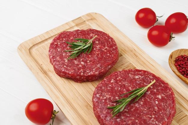 Dwa paszteciki burger surowej wołowiny na desce z bliska