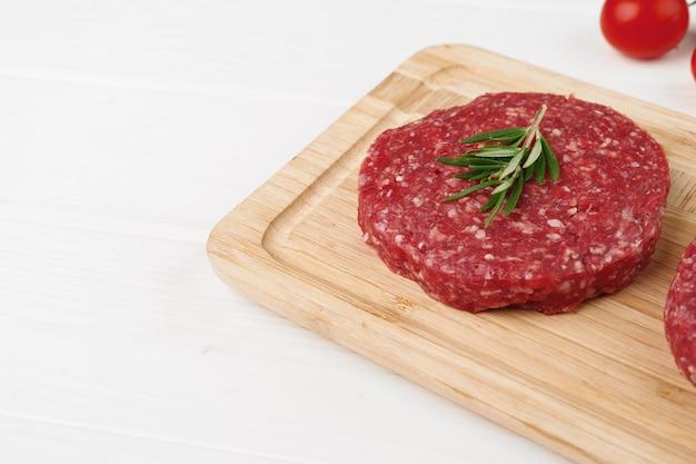 Dwa paszteciki burger surowej wołowiny na desce