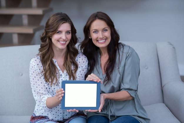 Dwa piękna kobieta trzyma cyfrową pastylkę