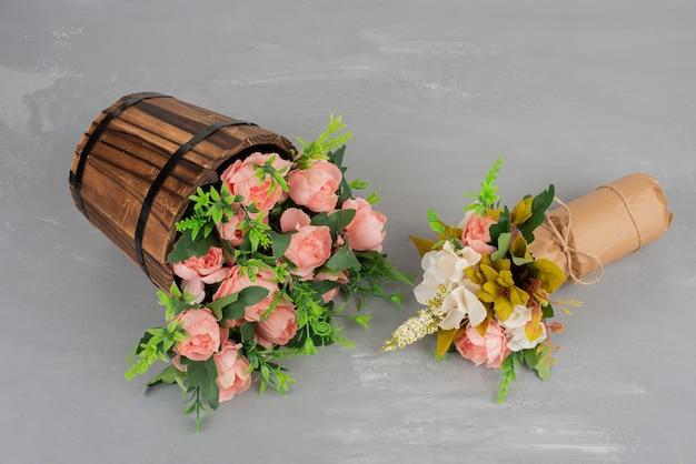 Dwa piękne bukiety kwiatów na szarej powierzchni.