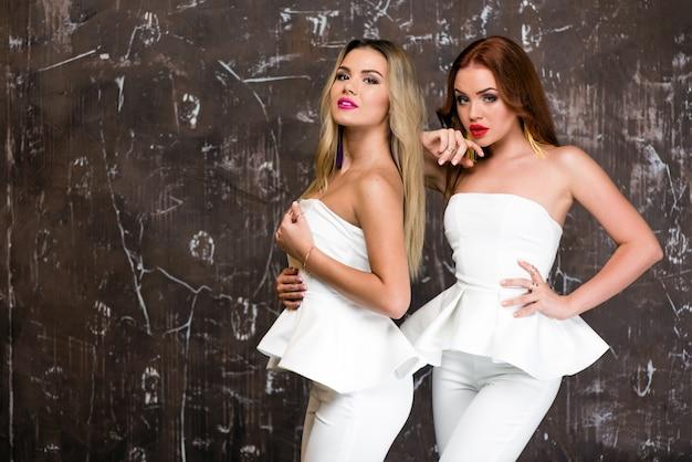 Dwa piękne modele stoją w pobliżu brązowej ściany