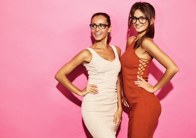 Dwa piękne uśmiechnięte kobiety modelki noszą bawełnianą sukienkę o modnym designie, swobodny letni styl na randkę na spacerze. brunetka bizneswomanu kobiety pozuje na menchii ścianie