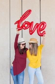 Dwa pięknej młodej kobiety ma zabawę na zewnątrz z czerwonym balonem z kształtem słowa miłości. codzienne ubrania. noszą czapki i nowoczesne okulary przeciwsłoneczne. l styl życia na świeżym powietrzu