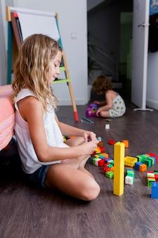 Dwa pięknej rodzeństwa siostry bawić się z budowy zabawkarskimi blokami buduje wierza w domu. dzieci bawiące się. dzieci w przedszkolu. dziecko i zabawki. rodzinny styl życia