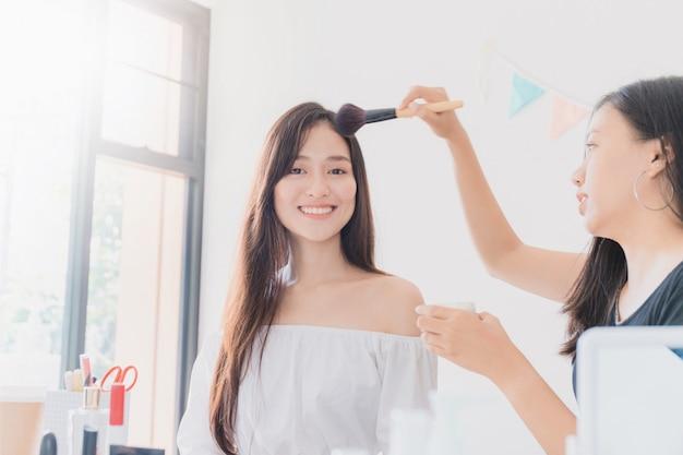 Dwa piękny azjatykci kobiety blogger pokazuje dlaczego uzupełniać i używać kosmetyki. przed kamerą do nagrywania wideo vlog w domu.