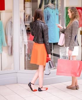 Dwa pięknych kobiet nadokienny zakupy w centrum handlowym