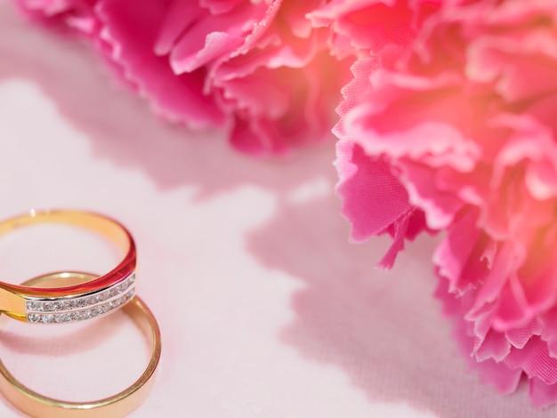 Dwa pierścienie z różowym kwiatem na ślub