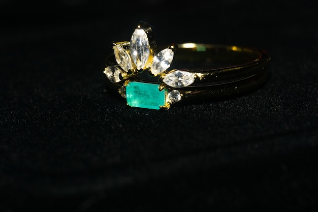 Dwa pierścionki z żółtego złota z białymi cyrkoniami i turmalinem paraiba.