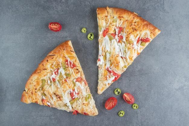 Dwa plasterki pysznej pizzy z pomidorami cherry