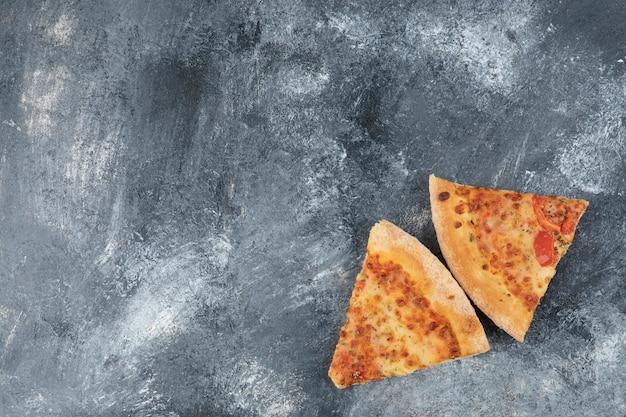 Dwa plasterki pysznej świeżej pizzy na kamiennym tle.