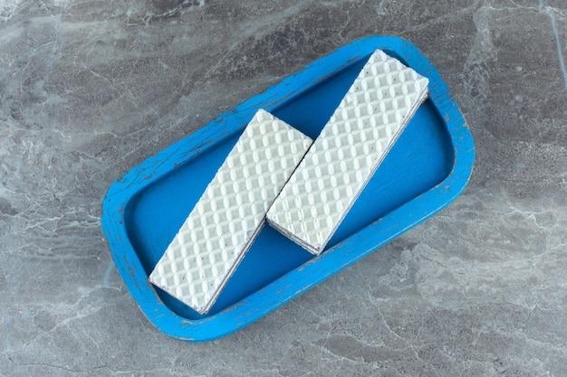 Dwa plasterki wafla na niebieskiej desce.