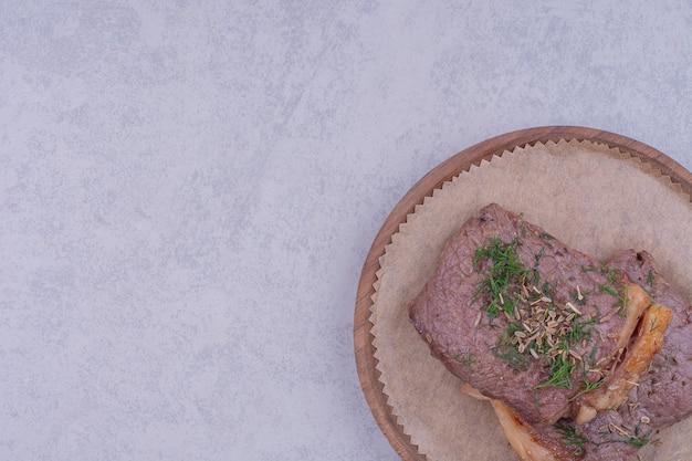 Dwa plastry steku z ziołami i przyprawami na drewnianym talerzu.