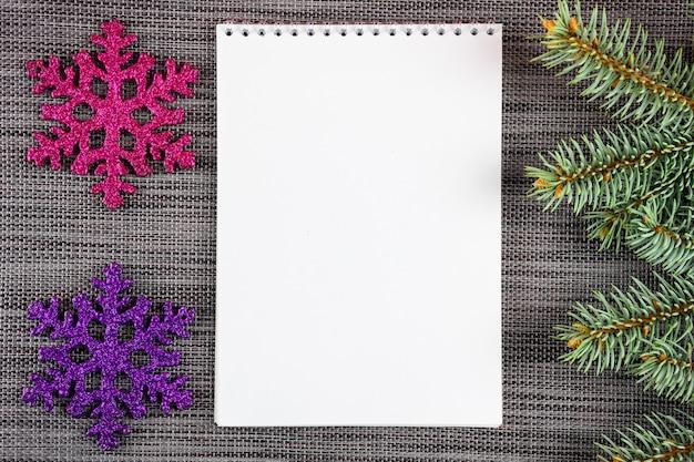 Dwa płatki śniegu, gałąź choinki, notatnik z białą kartką na tle nowego roku.