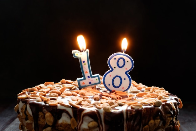 Dwa płonącej świeczki na urodzinowym torcie na czarnym tle