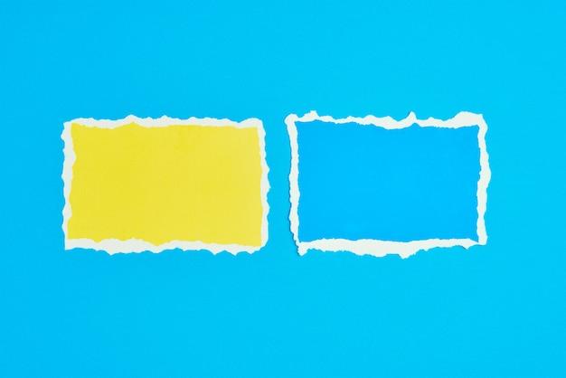 Dwa podarte arkusze poszarpane krawędzie papieru na niebieskim tle. szablon z kawałkiem kolorowego papieru