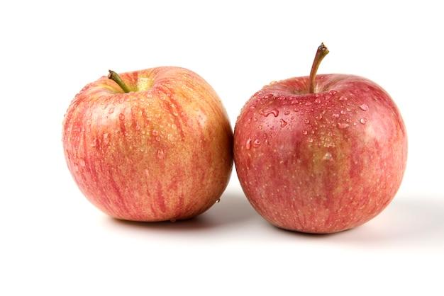 Dwa pojedyncze całe czerwone jabłko na białym tle